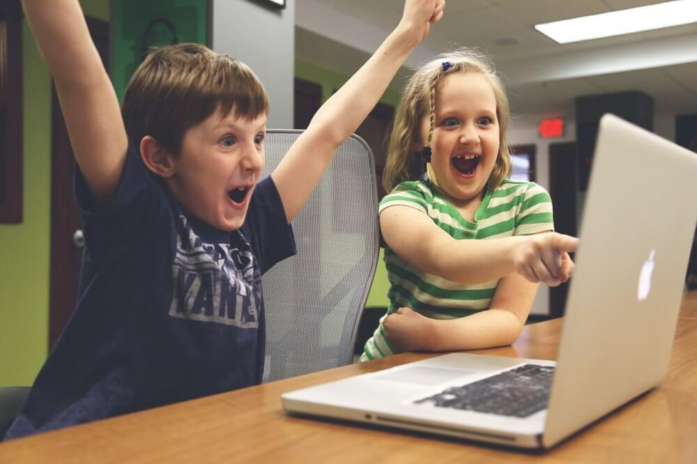 Children getting way too excited about something on a computer screen.